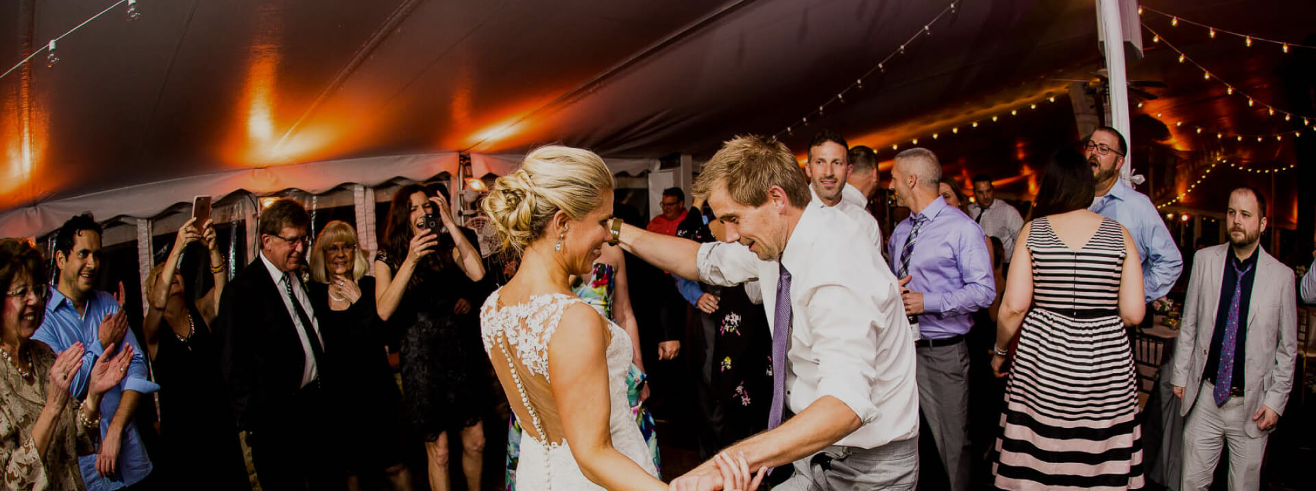 bride and groome dancing at their wedding, surrounded by friends and family
